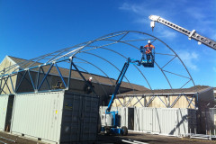 Installing fabric structures in Melbourne with false wall on containers.