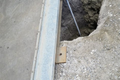 """Containers chocked to level, brackets welded with """"J"""" rods, then concrete poured"""
