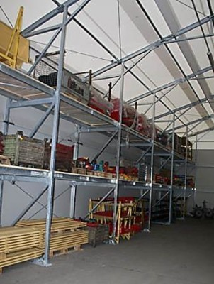 Space saving pallet racking between wall posts for warehouses and hangars.