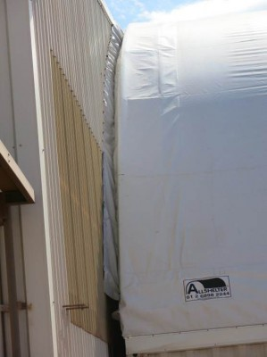 Using a joining strip to attach a fabric structure to an existing building.